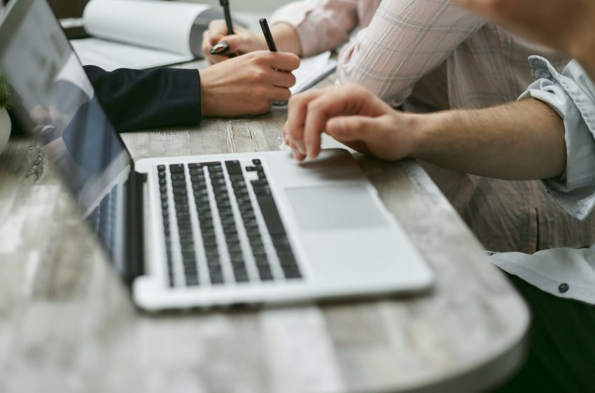 unrecognizable coworkers using netbook and writing information on papers